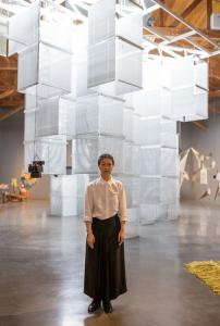 Haegue Yang in front of her work Sol LeWitt Upside Down – K123456, Expanded 1078 Times, Doubled and Mirrored, 2015, installation view kurimanzutto, Mexico City. © Haegue Yang, courtesy kurimanzutto, Mexico City, photo: Abigail Enzaldo.